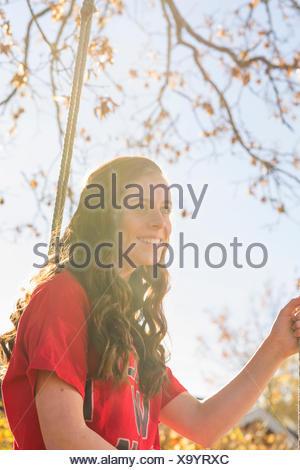 Sweden, Sodermanland, Stigtomta, Teenage girl (14-15) sitting on tree swing in sunlight - Stock Photo