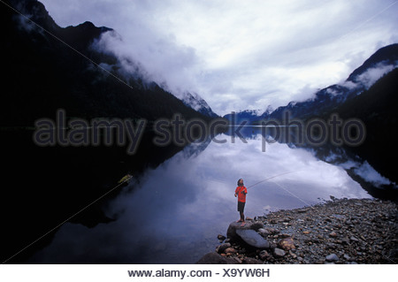 Man fly fishing in quiet lake in a large valley. - Stock Photo