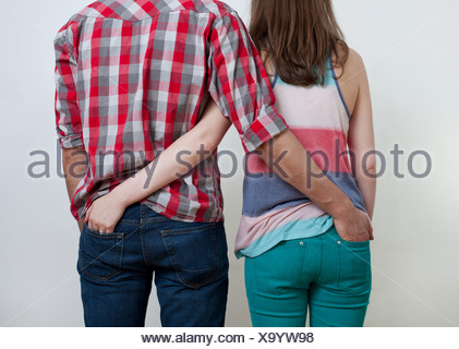 Young couple with hands in each other's back pockets - Stock Photo