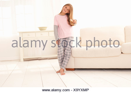 Girl in pajamas leaning on couch - Stock Photo