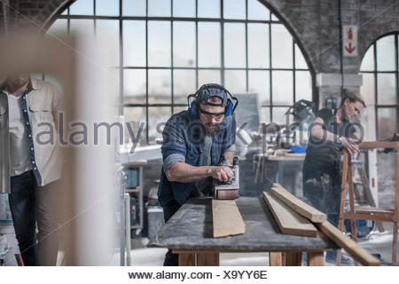 Carpenter sanding wood in antique restoration workshop - Stock Photo