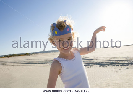 Girl wearing crown on beach - Stock Photo