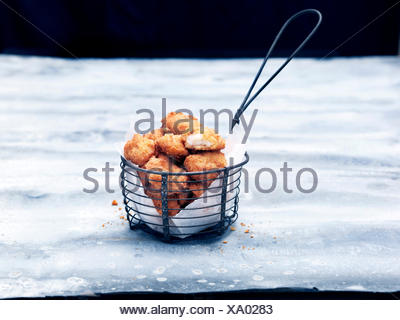 Frying basket full of breaded Scottish wholetail scampi - Stock Photo