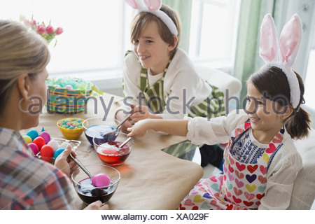 Children and mother coloring Easter eggs at table - Stock Photo