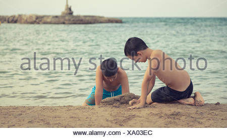 Two children playing in sand on beach, Barcelona, Spain - Stock Photo
