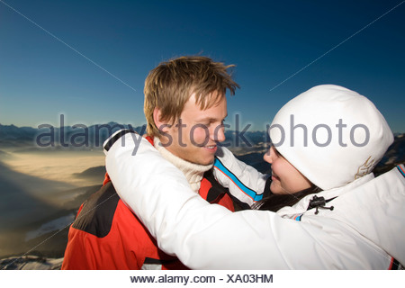 young couple in the mountains tenderly looking at each other - Stock Photo