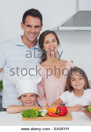 Beautiful family standing in the kitchen - Stock Photo