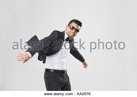 Smiling man in tuxedo dancing - Stock Photo