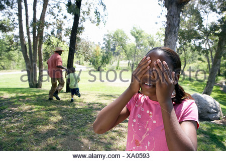 Grandfather playing hide and seek with two grandchildren 5 10 in park girl covering eyes - Stock Photo
