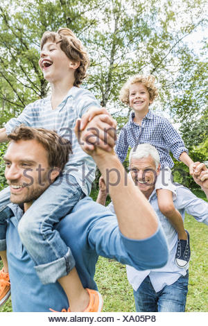 Mid adult man with father giving sons shoulder carry in garden - Stock Photo