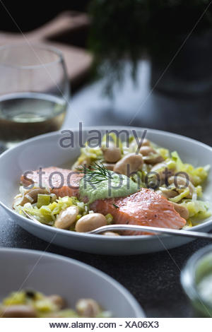 A plate full of white butter beans topped with oven baked salmon slices is photographed from the front view. - Stock Photo
