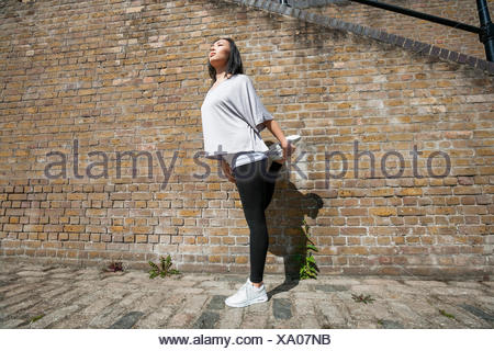 Full length of young fit woman stretching against brick wall - Stock Photo