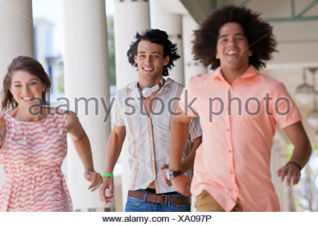 Happy friends running along outdoor corridor - Stock Photo