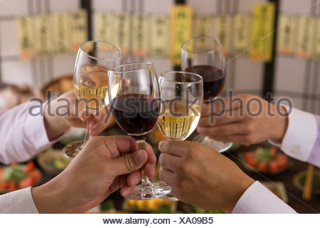 Four People Toasting with Wine at Izakaya - Stock Photo