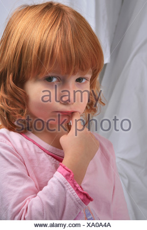little redhaired girl in pyjama sulking doesn't want to go to bed - Stock Photo