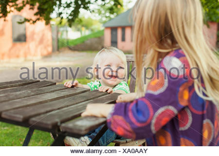 Happy baby boy looking at sister while sitting in park - Stock Photo
