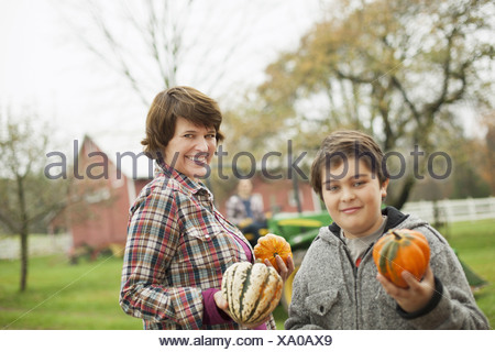 Two people a woman and a child on an organic farm carrying harvested vegetables squashes and pumpkins Organic farming - Stock Photo