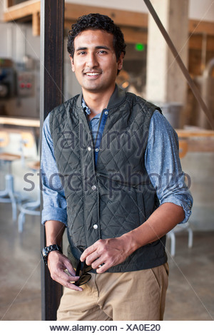 Portrait of young man leaning against wooden post - Stock Photo