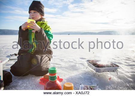 Boy (8-9) drinking tea outdoors - Stock Photo