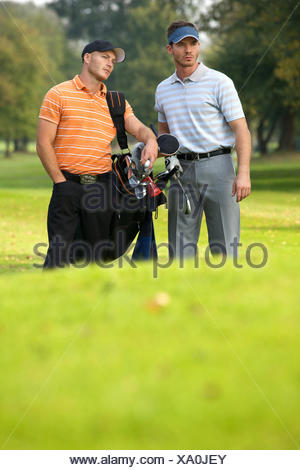 Young men standing on golf course carrying bags - Stock Photo