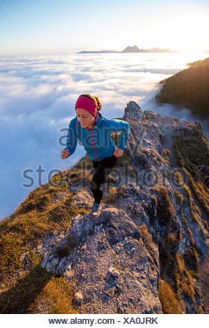 Young woman running along a mountain ridge, Salzburg, Austria