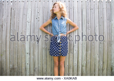Portrait of teenage girl in front of wooden fence - Stock Photo