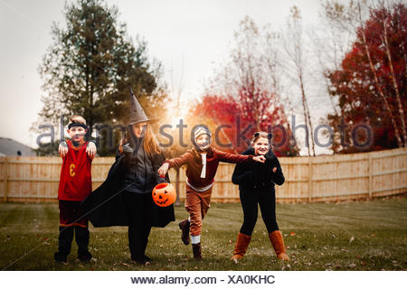 Portrait of boy and girls posed in halloween costumes in garden at sunset - Stock Photo
