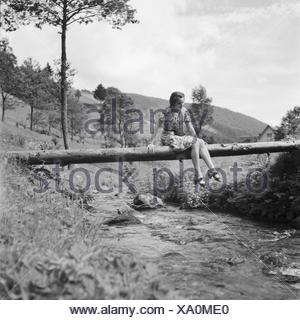 Eine junge Frau überquert einen Bach im Schwarzwald, Deutschland 1930er Jahre. A young woman crossing a creek in the Black Forest area, Germany 1930s. - Stock Photo