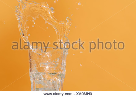 Water being poured into glass, spilling over, close up - Stock Photo