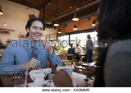 Smiling couple dining at restaurant table - Stock Photo