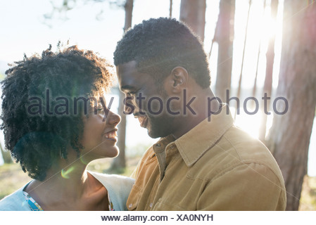 A happy couple in a shady spot in woodland in summer Hugging and holding each other - Stock Photo