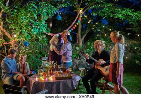 Three couples enjoying evening garden party - Stock Photo