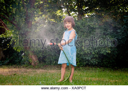 Little girl with garden hose - Stock Photo
