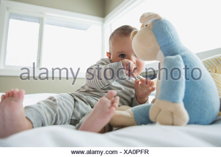 Baby with stuffed animal on bed - Stock Photo