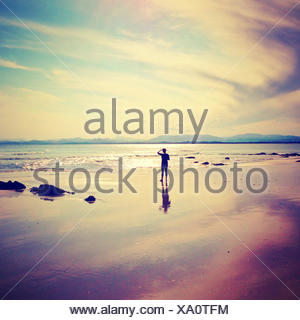 Silhouette of a man standing on beach looking out to sea - Stock Photo