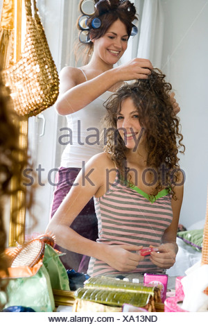 Young women styling hair in rollers - Stock Photo