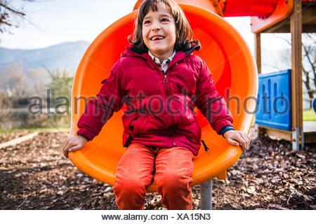 Boy sitting on orange playground slide - Stock Photo