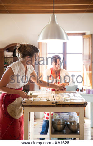 Young woman applying dried lavender to soap bars in handmade soap workshop - Stock Photo