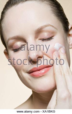 A serene woman applying moisturizer on her cheek - Stock Photo