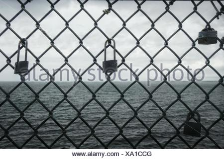 Padlocks Attached On Chainlink Fence By Sea - Stock Photo