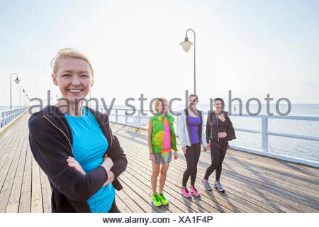 Group of women in sports clothing standing on jetty - Stock Photo