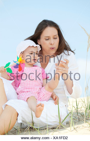Germany, Bavaria, Mother blowing baby girl's feet - Stock Photo