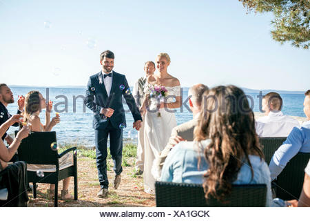 Bride and groom at wedding ceremony on beach - Stock Photo