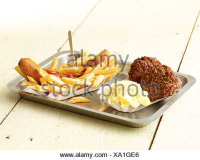 Curry sausage with French fries, two meatballs and mashed potatoes on metal tray - Stock Photo