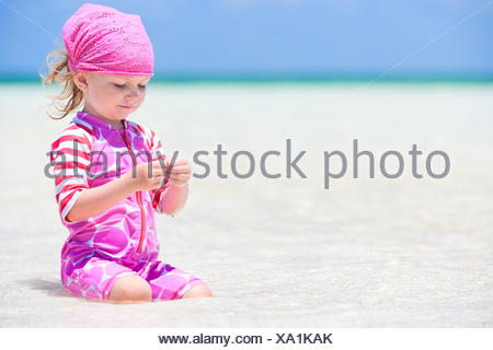 little girl at tropical beach playing in shallow water, Mexico - Stock Photo