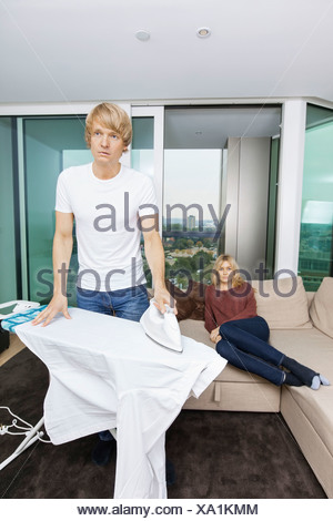Man ironing shirt while woman sitting on sofa at home - Stock Photo
