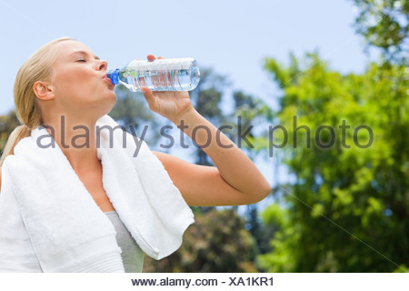 Side view of sportswoman drinking water - Stock Photo