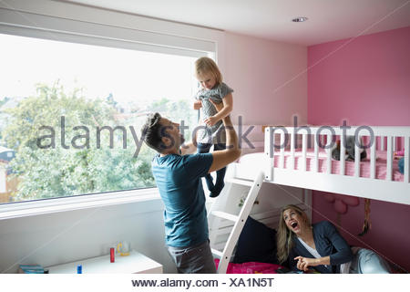 Affectionate father lifting toddler daughter in bedroom - Stock Photo