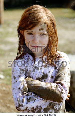 Child totally covered in mud, dirty, wild, untypical girl - Stock Photo