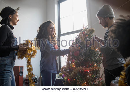 A group of people decorating a Christmas tree - Stock Photo